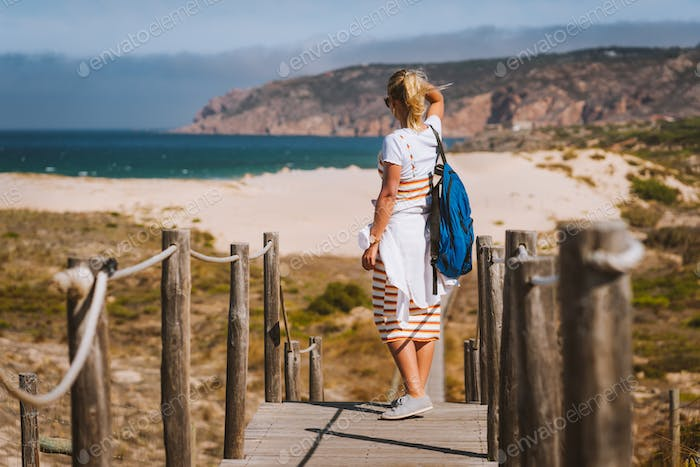 Adult female tourist enjoying costal view of Praia do Guincho Beach. Cascais, Portugal. This is