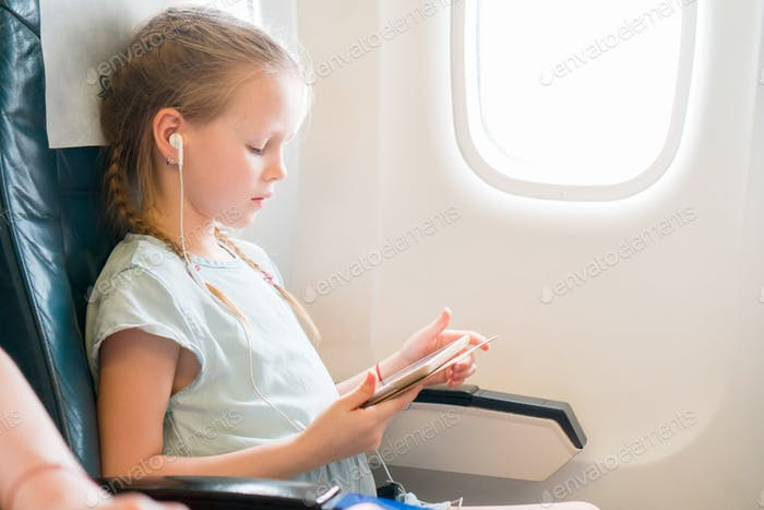 Adorable little girl traveling by an airplane. Cute kid with laptop near window in aircraft