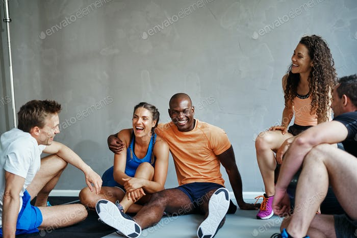 Diverse friends in sportswear sitting together in a gym laughing
