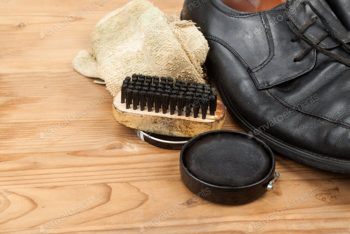 Shoe polish with brush, cloth and worn men shoes on wooden platf