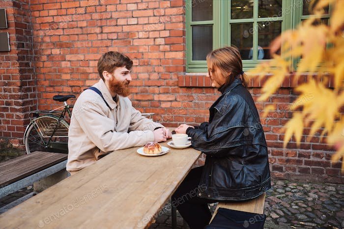 Young beautiful couple happily resting together drinking coffee in street cafe