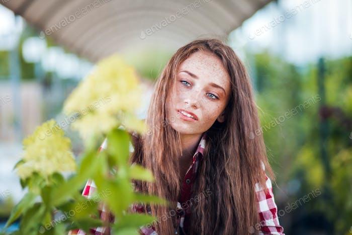 Gardener woman looking at plants in a garden center