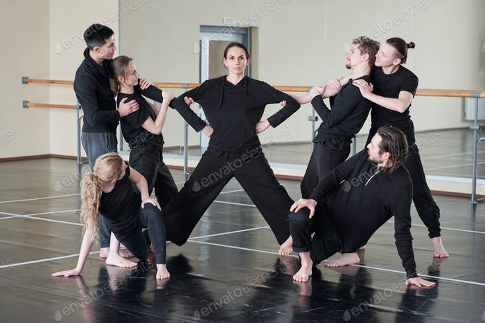 Woman with outstretched legs and group of young people exercising together