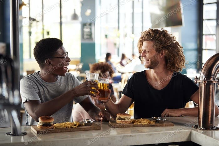 Two Male Friends Eating Food And Drinking Beer In Sports Bar