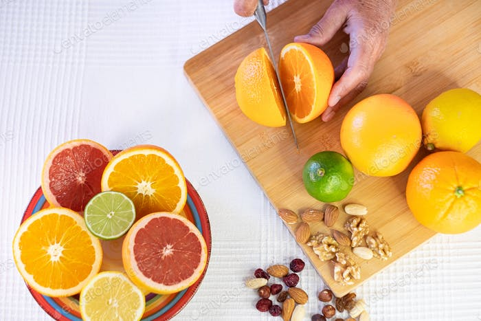 Group of whole and halved citrus fruits, wooden cutting board with female hand cutting an orange