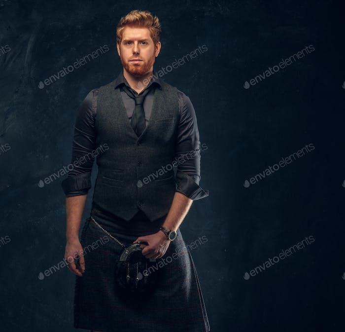 Рыжий человек, одетый в элегантный жилет с галстуком и килтом в студии на фоне темной текстурированной стены