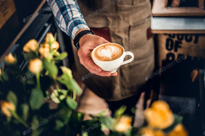 A man holds a coffee with a heart foam top view.