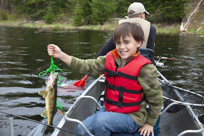 Junge Fischer in einem Kanu hält erste Zander des Tages