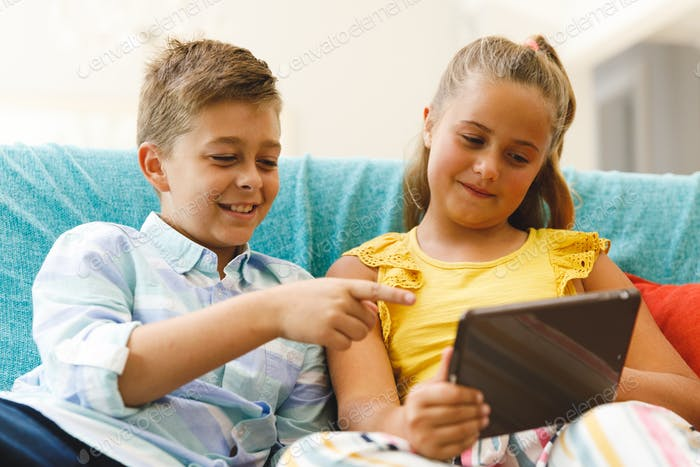 Happy caucasian brother and sister sitting on couch and using tablet in living room