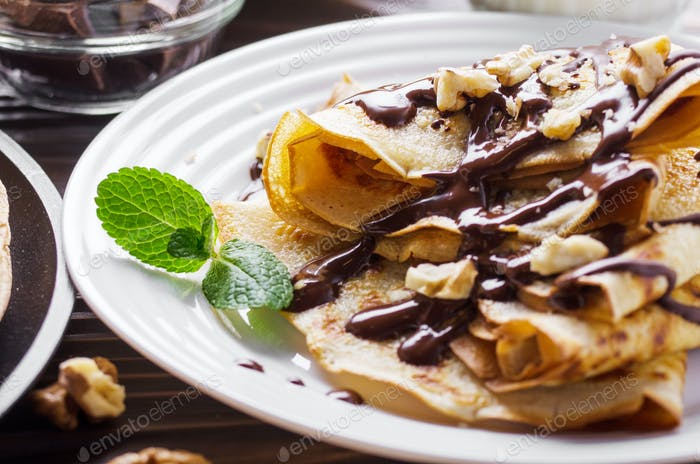 French crepes with chocolate sauce and walnuts in ceramic dish o