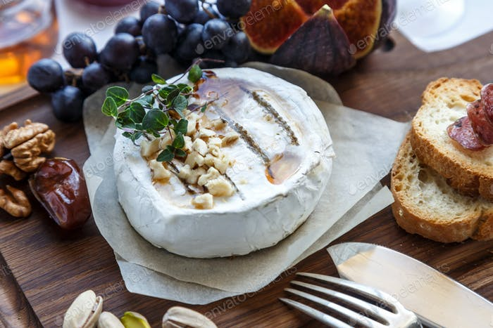 Camembert cheese with figs, honey and wine. Selective focus. Close view