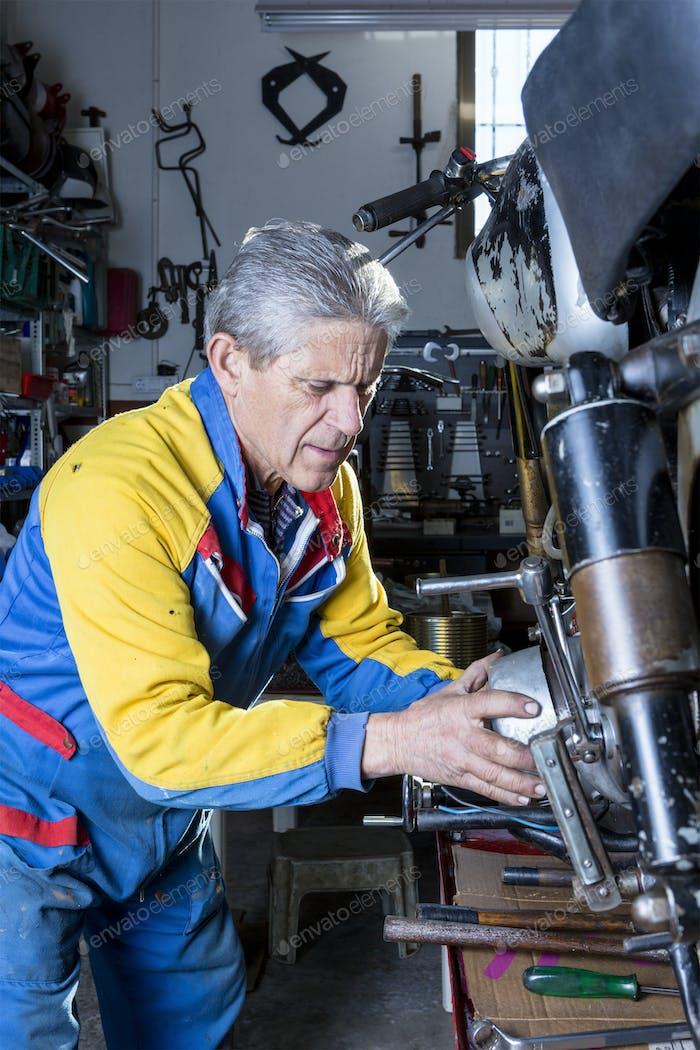 mechanic repairing a motorbike engine