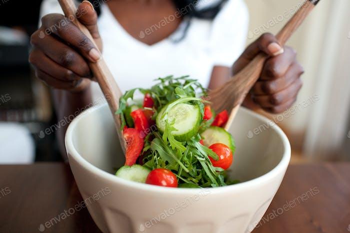 Ethnische Frau, die einen Salat zubereitet