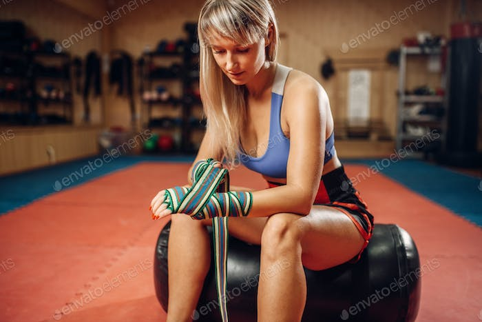 Female kickboxer sitting on punching bag in gym