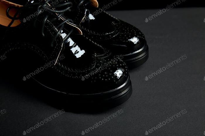Woman female black oxford platform shoes on black background.