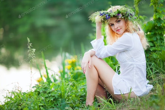 Young beautiful blond woman in white mini dress and floral wreath sitting near lake and smiling on