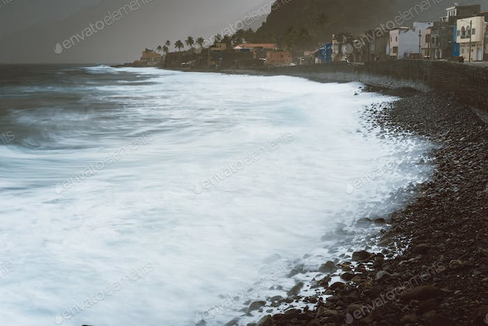 Long exposure foam ocean waves with blowing spray on rocky volcanic shore. Dwellings on Ribeira