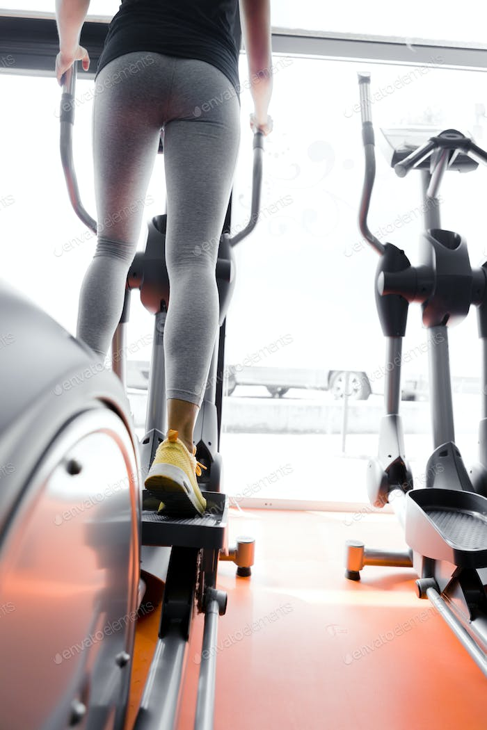 Closeup shot of legs of a female using elliptical trainer
