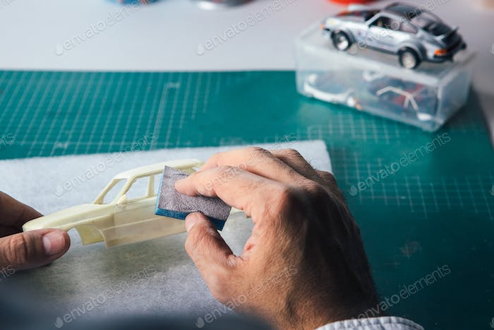 Unrecognizable person polishing slot car