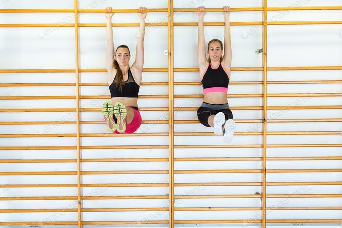 Two sporty young woman doing aerobic class on a fitness center.
