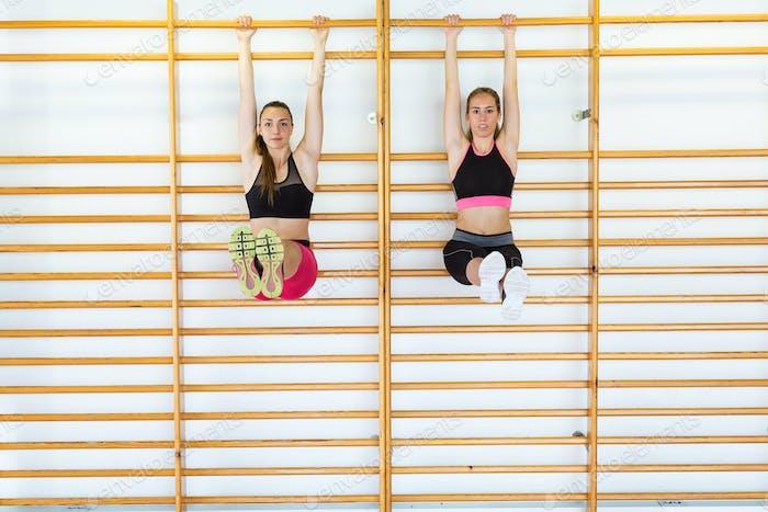 Deux jeunes femmes sportives faisant des cours d'aérobie sur un centre de fitness.