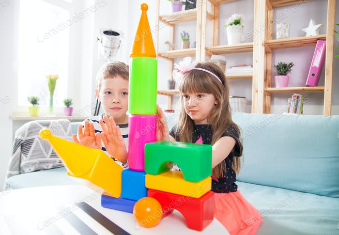 Siblings playing with colorful blocks at home, happy family
