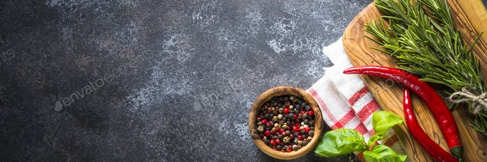 Olive oil, herbs and spices on a dark stone table
