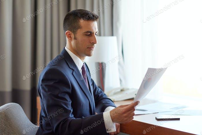 Geschäftsmann mit Papieren arbeiten im Hotelzimmer