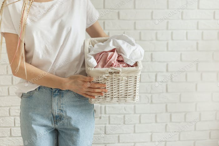 Woman holding wicker basket with heap of different clothes, on bricks wall background