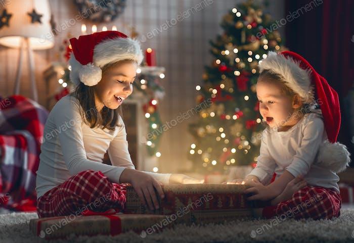 Kinder öffnen Weihnachtsgeschenke