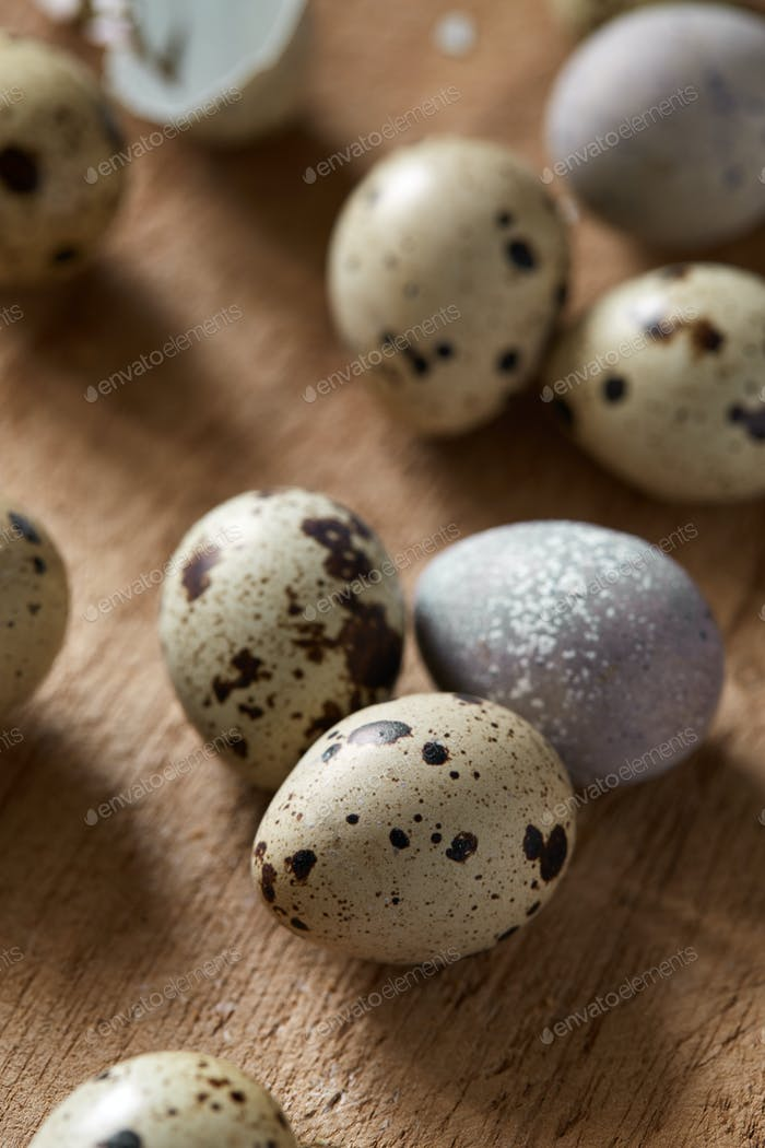 Top flatview of quail eggs on old wooden cutboard
