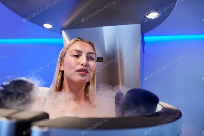Young woman in a full body cryotherapy cabinet