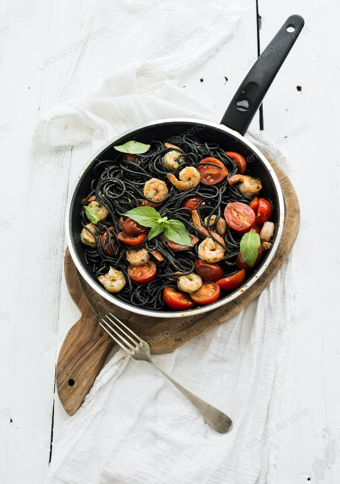 Black pasta spaghetti with shrimps, basil, pesto sauce and slow-roasted cherry-tomatoes