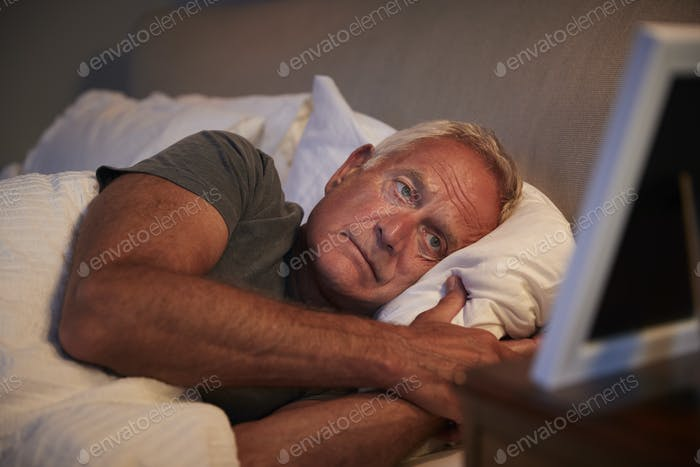 Sad Senior Man Lying In Bed Looking At Photo Frame