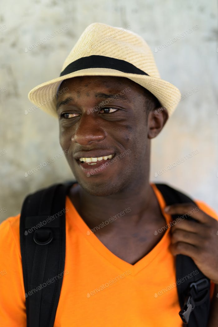 Face of happy young African tourist man smiling and thinking