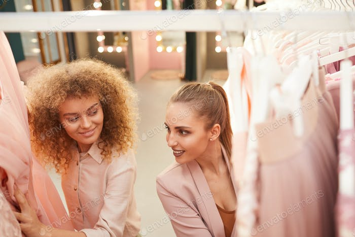 Two Young Women Choosing Dresses in Boutique