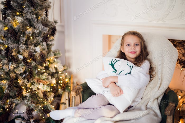Portrait of a cute little girl embracing cushion at home against christmas tree