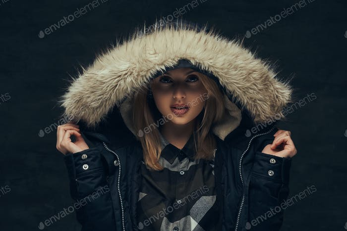 Portrait of a blonde girl in a winter jacket and fleece shirt, standing in a studio.