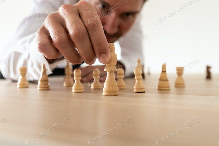 Geschäftsführer arrangiert Schachfiguren mit König in der Führungsposition