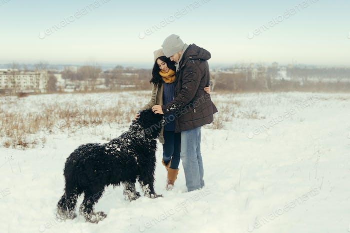 Junges Paar zu Fuß mit einem Hund in einem Wintertag