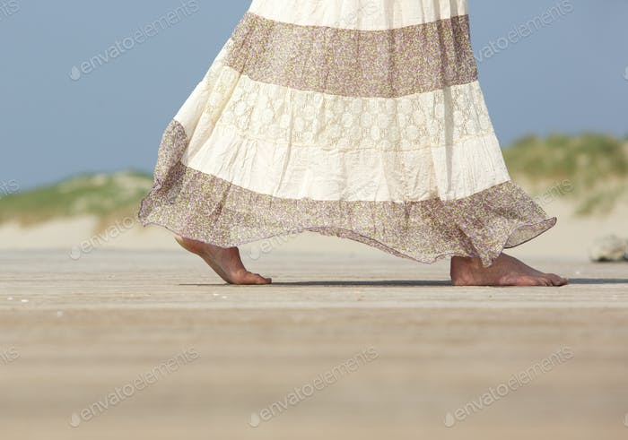 Female walking barefoot at the beach