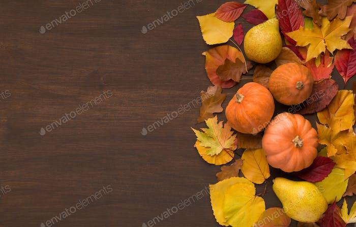 Autumn foliage with three decorative pumpkins on wood