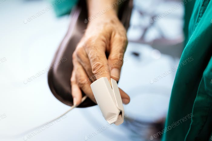 Patient with pulse oximeter on finger for monitoring during surgery