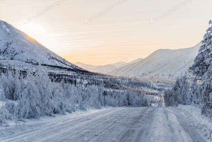 beautiful snow covered winter road with road sign and trees in mountains, kolyma highway