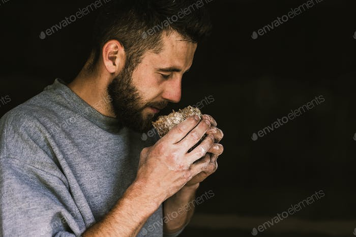 Close up of a young bearded man smelling delicious freshly baked bread