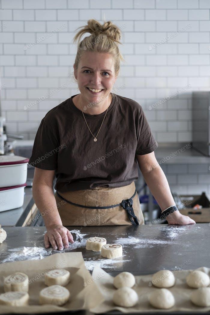 Woman working in a kitchen, preparing danish pastries dough.