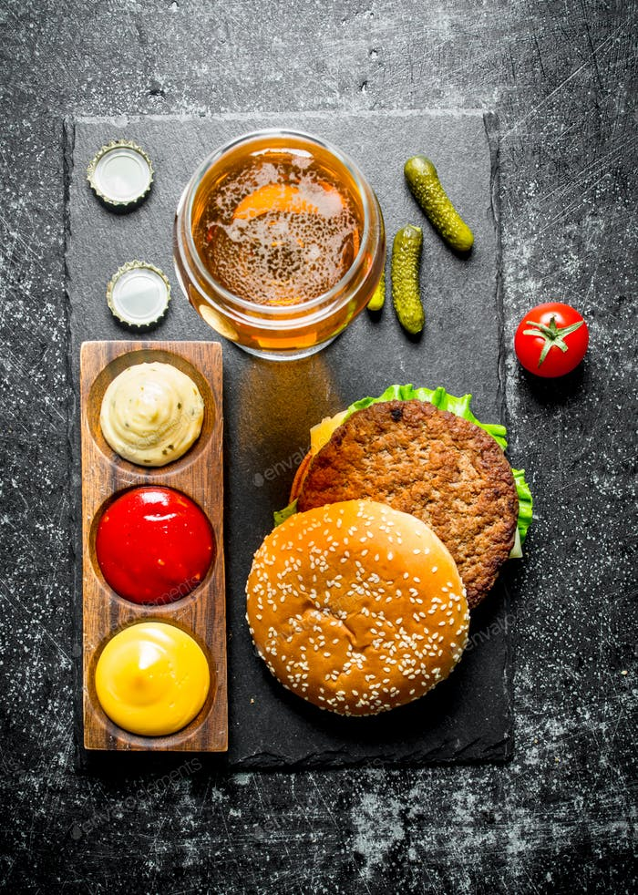 Burger with beer, sauces and gherkins.
