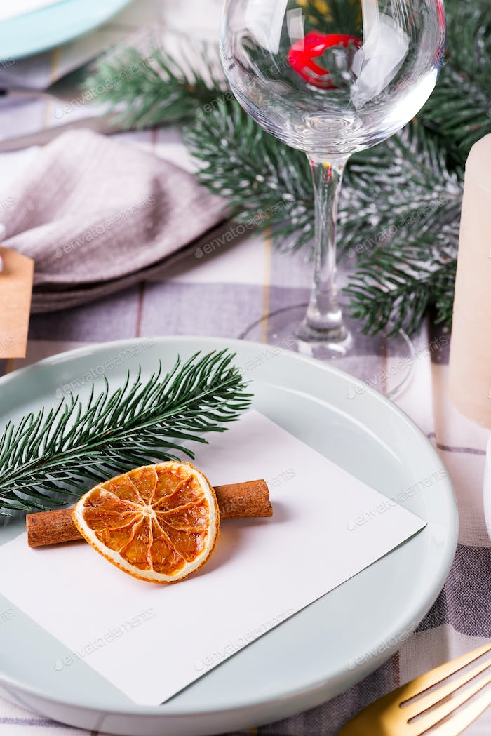 Festive Christmas and New Year details table setting with dry orange and cinnamon on a gray textile