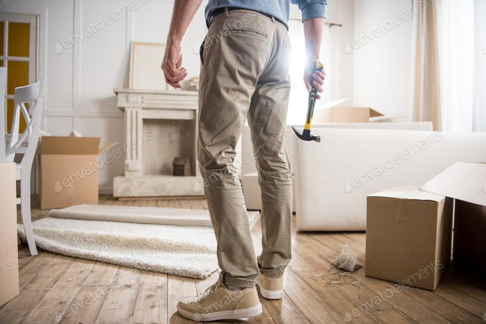 rear view of casual man with hammer standing in the room