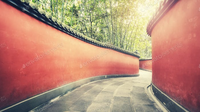 Curvy red walls passage surrounded by bamboo forest.